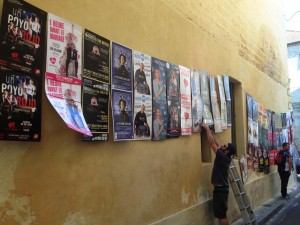 Affichage au Festival d'Avignon 2014 sur un mur avec des ficelles tendues et une échelle