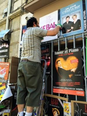 """David Lepole sur une échelle pose les affiches """"Le Bal"""", """"Un jour c'était la nuit"""" et """"Amour et Piano"""" au Festival d'Avignon"""