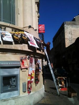 Un afficheur sur une échelle pose des affiches en hauteur au Festival d'Avignon 2014